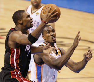 Miami's Chris Bosh (1) goes past Oklahoma City's Serge Ibaka (9) during Game 2 of the NBA Finals between the Oklahoma City Thunder and the Miami Heat at Chesapeake Energy Arena in Oklahoma City, Thursday, June 14, 2012. Photo by Nate Billings, The Oklahoman