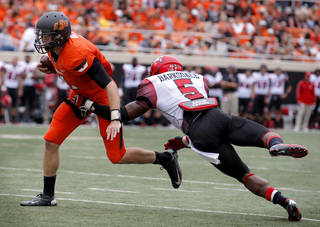 Oklahoma State's J.W. Walsh (4) gets by Louisiana-Lafayette's Darius Barksdale (5) during a college football game between Oklahoma State University (OSU) and the University of Louisiana-Lafayette (ULL) at Boone Pickens Stadium in Stillwater, Okla., Saturday, Sept. 15, 2012. Photo by Sarah Phipps, The Oklahoman