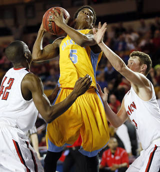 Putnam City West's Omega Harris (5) tries to take a shot between Union's Jeff Mead (42), left, and Alex Barton (11) during the Class 6A boys championship game in the state high school basketball tournament between Putnam City West and Tulsa Union at the Mabee Center in Tulsa, Okla., Saturday, March 15, 2014. Photo by Nate Billings, The Oklahoman