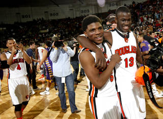Stephen Clark, left, and Tre Banks, of Douglass High School, celebrate March 10 after the Trojans beat Anadarko 86-53 to win the Class 4A boys basketball championship at State Fair Arena in Oklahoma City. Photo by Bryan Terry, The Oklahoman Bryan Terry