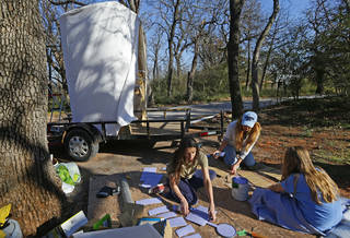 Sisters Jennifer Teel, left, and Kimberly Leeper paint pieces of cardboard with Teel's daughter, Sarah, 10, as they build the Forever After Parties float for Saturday's St. Patrick's Day parade in Oklahoma City. Photos by Bryan Terry, The Oklahoman
