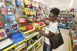 Andrea Greene, of Moore, looks at a school supply checklist in August while shopping for her two children on the school supply aisle at Dollar General in Moore. Photo by Paul B. Southerland, The Oklahoman Archives PAUL B. SOUTHERLAND - PAUL B. SOUTHERLAND