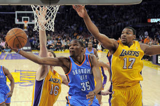 Oklahoma City Thunder forward Kevin Durant, center, puts up a shot as Los Angeles Lakers forward Pau Gasol, left, of Spain, and center Andrew Bynum defend during the first half of an NBA basketball game, Thursday, March 29, 2012, in Los Angeles. (AP Photo/Mark J. Terrill) ORG XMIT: LAS101