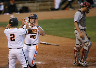 OSU's Zach Fish, center, and Tim Arakawa celebrate beside OU's Mac James after scoring in the fourth inning of a Bedlam baseball game between the University of Oklahoma and Oklahoma State University at Chickasaw Bricktown Ballpark in Oklahoma City, Thursday, May 15, 2014. Photo by Bryan Terry, The Oklahoman