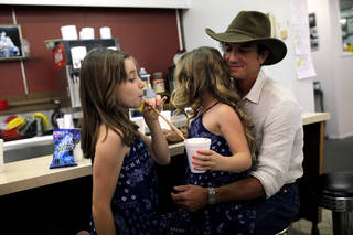 The Red Dirt Rangers' Brad Piccolo eats ice cream Friday with his daughters Isabel, 9, right, and Ruby, 7, at Sooner Drug Store & Gifts during the Woody Guthrie Festival in Okemah. SARAH PHIPPS