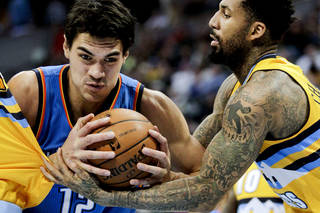 Steven Adams left, tries to drive past Denver Nuggets' Wilson Chandler during a game in Denver. AP Photo