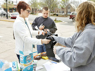 Sharon Trimble hands some trash bags to Sam Meyers and his grandmother Karen Meyers during Edmond's annual Operation Clean Streets event in downtown Edmond, OK, Saturday, April 20, 2013, By Paul Hellstern, The Oklahoman