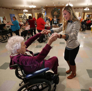 University of Oklahoma student Annabelle Irvin dances with Grace Living Center resident Jerri Melton, 102, at a special holiday dance organized by members of the Kappa Alpha Theta sorority. PHOTO BY STEVE SISNEY, THE OKLAHOMAN