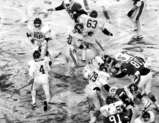 "OU tight end Keith Jackson (88) prepares to take a handoff from quarterback Jamelle Holieway (4) during the ""Ice Bowl"" Bedlam college football game against OSU in 1985 in Stillwater, Okla., on Nov. 30, 1985. Among the OU blockers on the play were Eric Pope (63), Spencer Tillman (20), Lydell Carr (45) and Mark Hutson (79). Among the OSU defenders were John Washington (80) and Warren Thompson (91). Staff photo"