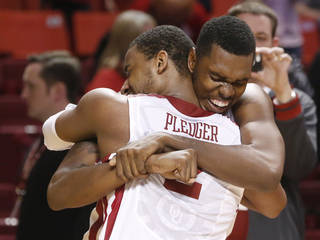 Oklahoma forward Andrew Fitzgerald, rear, hugs teammate Steven Pledger (2) following a 72-66 victory over Kansas in an NCAA college basketball game in Norman, Okla., Saturday, Feb. 9, 2013. (AP Photo/Sue Ogrocki)