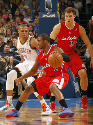 Oklahoma City Thunder point guard Russell Westbrook (0) defends on Los Angeles Clippers point guard Chris Paul (3) as Los Angeles Clippers power forward Blake Griffin (32) looks on during the NBA basketball game between the Oklahoma City Thunder and the Los Angeles Clippers at Chesapeake Energy Arena on Wednesday, March 21, 2012 in Oklahoma City, Okla. Photo by Chris Landsberger, The Oklahoman