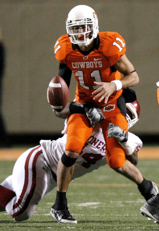 Oklahoma State's Zac Robinson (11) fumbles the ball under the pressure of Oklahoma's Jeremy Beal (44) during the second half of the college football game between the University of Oklahoma Sooners (OU) and Oklahoma State University Cowboys (OSU) at Boone Pickens Stadium on Saturday, Nov. 29, 2008, in Stillwater, Okla. STAFF PHOTO BY CHRIS LANDSBERGER