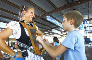 Valina Witte with the band Das its Lustig has David Vanburkleo play her washboard during Oktoberfest in the Park in Choctaw, Monday, September 3, 2012. Photo By David McDaniel/The Oklahoman