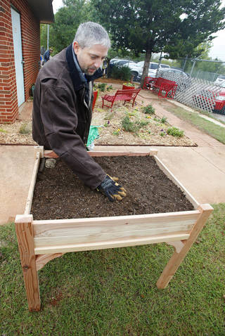 Volunteer Greg Sartin, of Moore, spreads soil in a raised planter at the Oklahoma Foundation for the Disabled during the United Way's annual Day of Caring in Oklahoma City. Volunteer projects included landscaping, painting, reading to children and working with seniors. Photo by Paul B. Southerland, The Oklahoman