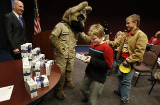 Darrell Weaver, director of the Oklahoma Bureau of Narcotics and Dangerous Drugs, and mascot Agent Roz watch while children at the J.D. McCarty Center pick out electronic gaming systems.