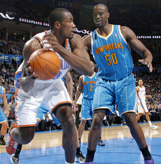 Oklahoma City Thunder power forward Serge Ibaka (9) gets a loose ball in front of New Orleans Hornets center Emeka Okafor (50) during the NBA basketball game between the Oklahoma City Thunder and the New Orleans Hornets at the Chesapeake Energy Arena on Wednesday, Jan. 25, 2012, in Oklahoma City, Okla. Photo by Chris Landsberger, The Oklahoman