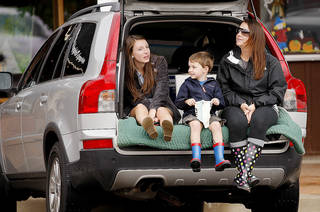 Spring Weems, at right, sits with her children, Madison, 15, a sophomore at Edmond Memorial, and Ashton, 4, as they wait for the Edmond Memorial High School homecoming parade. Photo by Bryan Terry, The Oklahoman
