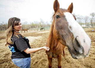 Natalee Cross pets a rescued horse. PHOTO BY CHRIS LANDSBERGER, THE OKLAHOMAN