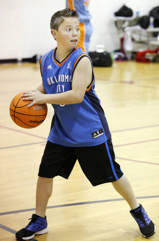 Dillon Smith, 11, looks to pass the ball during March Madness basketball camp at the YMCA in Bethany. Photo by Paul B. Southerland, The Oklahoman PAUL B. SOUTHERLAND - PAUL B. SOUTHERLAND