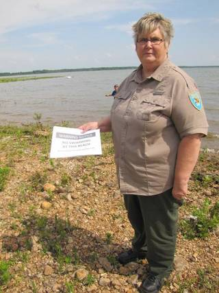 State park employee Sherri Burris is pictured with warning signs she was passing out to visitors of Bernice State Park on Tuesday after unsafe levels of E. coli found was found in water samples. Burris was telling swimmers to get out of the water before closing the park. SHEILA STOGSDILL/Tulsa World