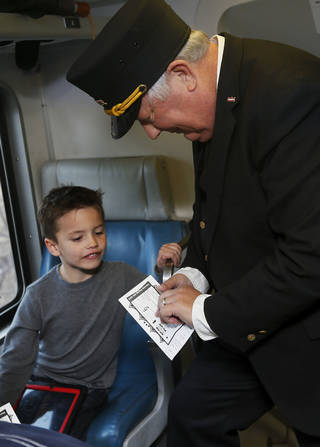 Conductor Neil Bagaus of Orlando, Fla., punches the train ticket of Lex McNeil of Jenks, Okla., on a demonstration ride of the Eastern Flyer passenger train from Sapulpa to the Oklahoma City metro area, Sunday, Feb. 23, 2014. Photo by Nate Billings, The Oklahoman