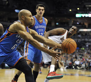 Oklahoma City Thunder's Derek Fisher (6) grabs a rebound as teammate Steven Adams and Milwaukee Bucks' Ekpe Udoh fight for position during the first half of an NBA basketball game Saturday, Nov. 16, 2013, in Milwaukee. (AP Photo/Jim Prisching)