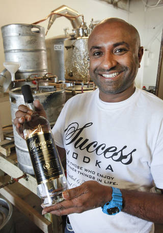 Alvin Philipose, owner of Twister Distillery in Moore, shows off a bottle of Success Vodka before the flash flame Friday. Photo by David McDaniel, The Oklahoman David McDaniel -