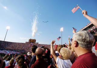 """University of Oklahoma football fans wave flags Sept. 11, 2004, during the national anthem at Gaylord Family — Oklahoma Memorial Stadium. Before each game, many OU fans shout """"home of the Sooners"""" at the end of the anthem. The chant is causing a controversy. Photo by Bryan Terry, The Oklahoman Archive"""