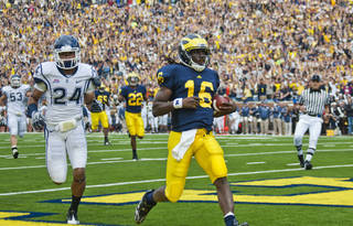 Michigan quarterback Denard Robinson (16) scores a touchdown, followed by University of Connecticut cornerback Dwayne Gratz (24), in the first quarter of an NCAA college football game, Saturday, Sept. 4, 2010, in Ann Arbor, Mich. (AP Photo/Tony Ding) ORG XMIT: MITD106