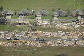 A row of lightly damages houses, top, face destroyed homes in a Vilonia, Ark., neighborhood Monday, April 28, 2014 after a tornado struck the town late Sunday, killing at least 16 people. (AP Photo/Danny Johnston)