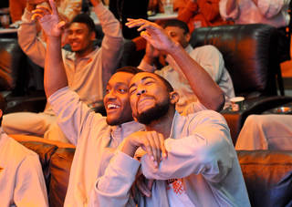 Oklahoma State basketball players Michael Cobbins (right) and Brian Willaims (behind) celebrate finding their seeding for the NCAA tournament at a watch party held in the team locker room inside Gallagher Iba Arena in Stillwater, Okla., on March 17, 2013. KT King/For the Tulsa World