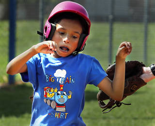 Vani Ellis, 10, dodges a tag at home plate as kids participate in a baseball camp sponsored by Norman Parks and Recreation Department at Whittier Recreation Center. PHOTO BY STEVE SISNEY, THE OKLAHOMAN STEVE SISNEY -