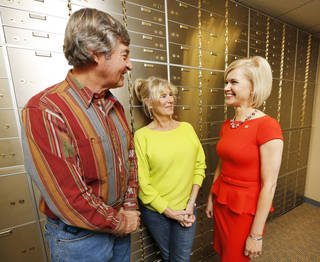 Larry and Mary Ann Marik talk Tuesday with Jill Castilla, right, executive vice president of Citizens Bank in Edmond. The Mariks travel to banks across the country. Photo By Steve Gooch, The Oklahoman