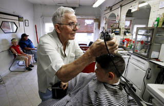 John Adkins gives a haircut to Colby Wyatt, 8, in his barbershop Tuesday in Maysville. Adkins cut hair for Colby's grandfather, Paul Arnold, when Arnold was 3 years old. Arnold is seated left with another grandson, Kaedon Wyatt, 10. Photo by Steve Sisney, The Oklahoman