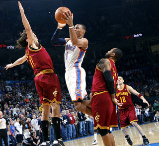 Oklahoma City's Russell Westbrook puts up a shot in front of Cleveland's Anderson Varejao (left) Mo Williams and Anthony Parker (background) during the first half of their NBA basketball game at the OKC Arena in Oklahoma City on Sunday, Dec. 12, 2010. The Thunder beat the Cavaliers106-77. Photo by John Clanton, The Oklahoman