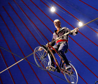 Circus performer Jim Decker uses a 19- foot pole to balance himself on a bicycle as he rides across a tightrope stretched 20 feet above the ground. Photo by Jim Beckel, The Oklahoman. Jim Beckel - THE OKLAHOMAN
