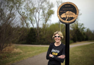 Camille Herron stands at the 16th mile marker of the Oklahoma City Memorial Marathon at Lake Hefner. Herron holds the women's course record in the marathon and has won 13 marathons in 10 different states. Photo by Sarah Phipps, The Oklahoman SARAH PHIPPS - SARAH PHIPPS