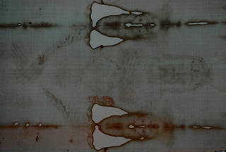 A detail of the Shroud of Turin, showing alleged images of the face (R) and hands (L) of Jesus Christ is displayed on public for the first time in ten years on April 10, 2010 in the Cathedral of Turin. Some two million people are expected to view one of the most revered relics in Christendom -- and among the most disputed -- over the next six weeks. AFP PHOTO / VINCENZO PINTO (Photo credit should read VINCENZO PINTO/AFP/Getty Images)