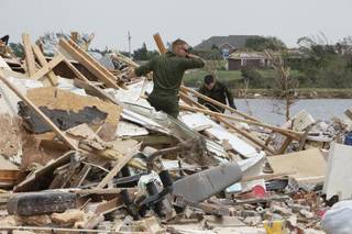 U.S. Marine Pfc. Dustin Buckner foreground, and Pfc. James Belohlavek help homeowner Kevin Roady on Falcon Lake in Piedmont on Friday. Buckner, who is from Cashion, got permission from his superiors to drive home with two friends and help those affected by the recent tornadoes. PAUL HELLSTERN