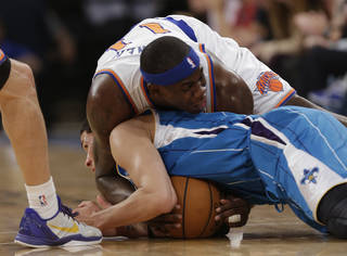 New York Knicks forward Ronnie Brewer (11) and New Orleans Hornets guard Austin Rivers (25) scuffle for a loose ball on the floor in the first half of their NBA basketball game at Madison Square Garden in New York, Sunday, Jan. 13, 2013. The dispute over control was settled with a jump ball at center-court. (AP Photo/Kathy Willens)