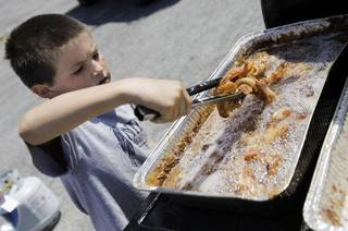 Tige Vanover (cq TIGE VANOVER), 9, of Enid, Okla., cooks bacon during Baconalia 2010, a bacon festival, in Enid, Okla., Saturday, August 28, 2010. Photo by Nate Billings, The Oklahoman ORG XMIT: KOD