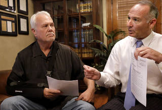 Brad Crawford, left, and his attorney, David Slane, display a court document in Slane's Oklahoma City law office Wednesday afternoon. Crawford is hopeful his name soon will be removed from the state's sex offender registry as a result of a state Supreme Court ruling Tuesday. Jim Beckel - THE OKLAHOMAN
