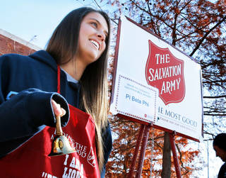 Jenna Geresi rings a bell at the Salvation Army donation kettle Tuesday at the University of Oklahoma. She and other volunteers from Pi Beta Phi sorority spent the day soliciting donations. PHOTO BY STEVE SISNEY, THE OKLAHOMAN