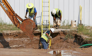 An Oklahoma City crew works on a sinkhole that formed when a water main broke at NW 2nd and Villa in Oklahoma City, Thursday, Sept. 5, 2013. A car fell into the sinkhole when it collapsed earlier in the afternoon. Photo by Nate Billings, The Oklahoman