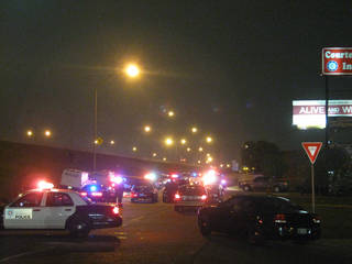 Law officers investigate a shoot-out with police that left two people dead near Interstate 35 and SE 44 Tuesday night. Photo by Matt Dinger, The Oklahoman