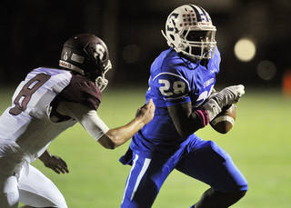 Eric J. Shelton/Reporter Stamford's James Washington (28) runs past Seymour's Zach Barton (8) during their game at Stamford on Friday, October 4, 2013.