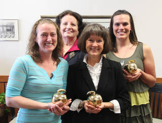 The Putnam City Public Schools Foundation presented Golden Apple Awards to four people in recognition of their service and dedication. Awards went to, from left, Barbara Brown, a custodian at Ralph Downs Elementary School; Catherine Carnline, the district?s director of homebound services; Esther Brazeal, kindergarten teacher at Overholser Elementary and Chantal Morris, PTA president and a volunteer at Wiley Post Elementary.