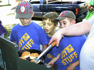 Jaden Jenkins, 10, William Carey, 9, and and Noah Davis, 9, all of Pack 65 in Harrah, look on as Troop 60 Assistant Scoutmaster Josh Dunn fries doughnuts the boys made. PHoto by Dana Garcia, for The Oklahoman Dana Garcia - Provided