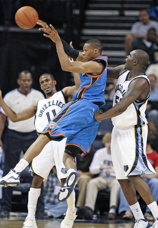 Thunder guard Russell Westbrook, center, gets a pass off under pressure from Grizzlies defenders Michael Conley, left, and Zach Randolph during the second half Wednesday. AP Photo