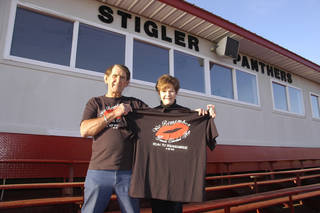 Billy and Joyce Cleveland of Stigler hold the shirt that runners from Stigler wear each year in the Oklahoma City Memorial Marathon in memory of their daughter, Pamela Cleveland Argo. PHOTO PROVIDED Photo provided